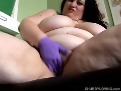 Huge fatty wears her purple rubber gloves before finger fucking