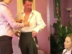 Two classy clothed ladies help a guy undress