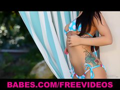 Gorgeous bikini-clad brunette strips down poolside