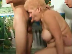 Old blonde babe entertaining two young cocks