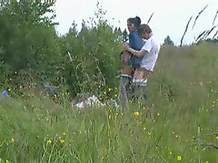 A lusty couple fucking in a field