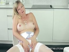 Cougar in stockings teasing vagina on a chair