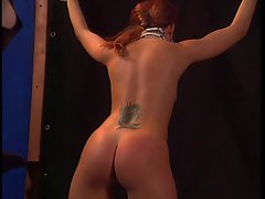 Dominatrix with red hair butt whips chick
